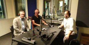 Nic in a radio station recording booth with Thom Armstrong and a radio host