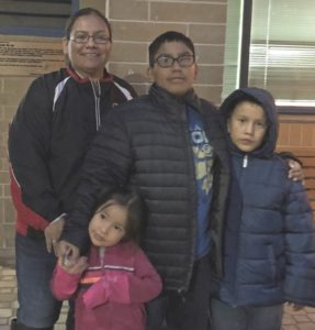 A family of four stand together in winter clothing outside a co-op.