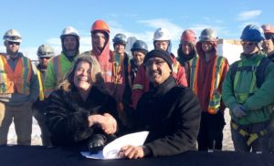 Two people smile into the camera shaking hands over a stack of papers, as a crowd of people in hard hats and visibility vests look on