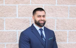 Irfaan, who has shortly clipped hair and beard, stands in front of a brick wall smiling and wearing a blue suit