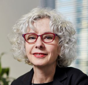 Headshot of Alexandra Wilson, a white woman with curly grey hair and red-framed glasses