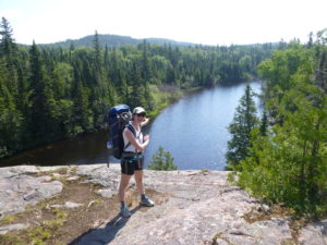 Cynthia stands on a cliff in hiking gear, gesturing out over a lake and trees